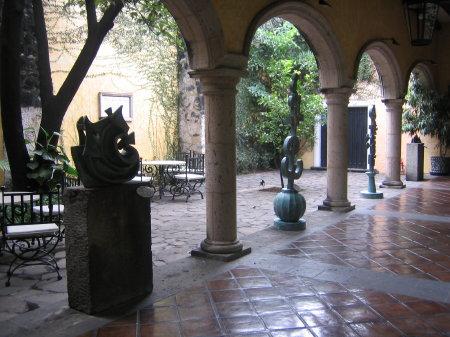 Statues are displayed in a restful patio in Mundo Cuervo.