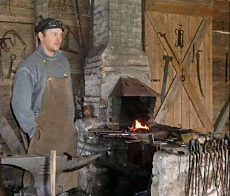 A costumed blacksmith works his trade at Highland Village